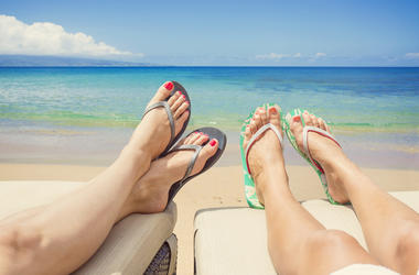 women lounging on beach in flip flops
