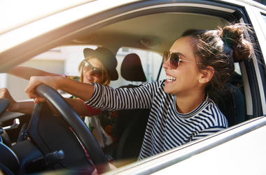 two girls driving laughing