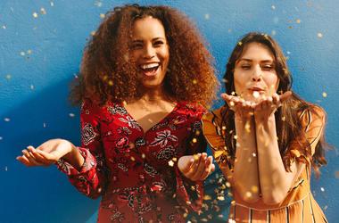 two women blowing glitter