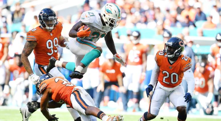 Dolphins running back Frank Gore leaps over Bears safety Adrian Amos.