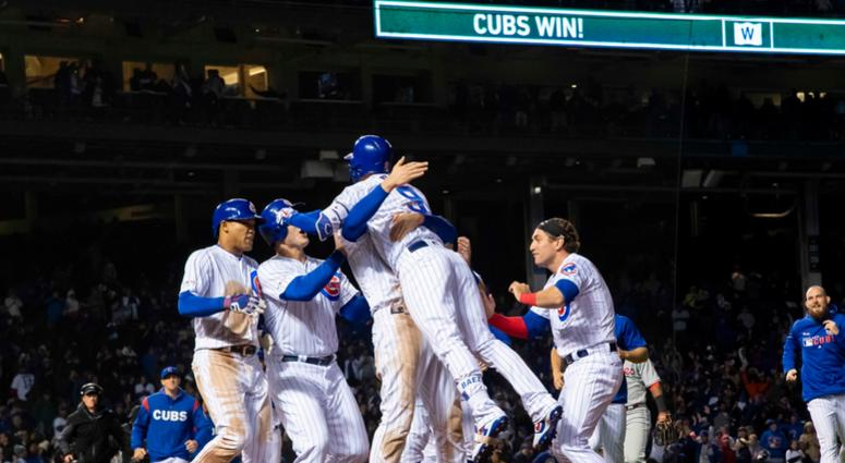 Cubs shortstop Javier Baez (9) celebrates his walk-off single against the Phillies with teammates.