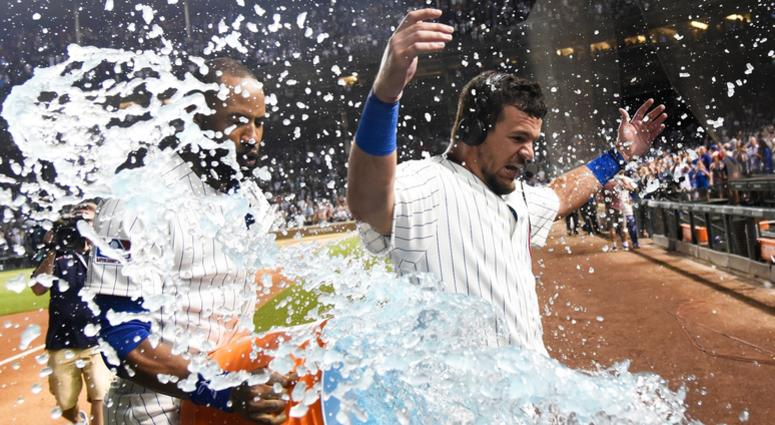 Cubs outfielder Kyle Schwarber is doused after hitting a walk-off homer against the Reds.