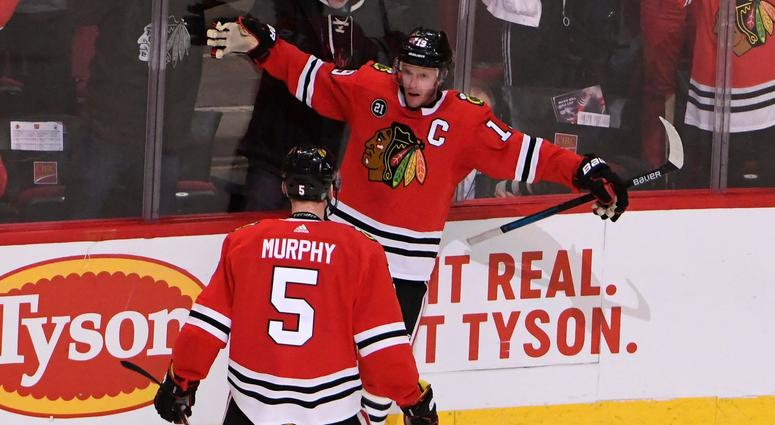 Blackhawks center Jonathan Toews (19) celebrates with defenseman Connor Murphy (5) after scoring the game-winning goal against the Canucks in overtime.