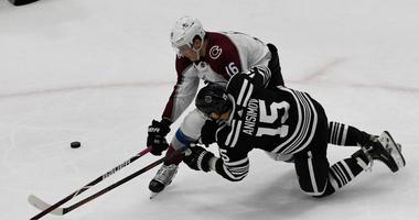 Blackhawks center Artem Anisimov (15) and Avalanche defenseman Nikita Zadorov (16) fight for the puck.