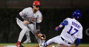 Reds infielder Alex Blandino tags out Cubs third baseman Kris Bryant.