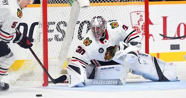 Blackhawks goaltender Cam Ward (30) makes a save as defenseman Connor Murphy (5) clears the puck.