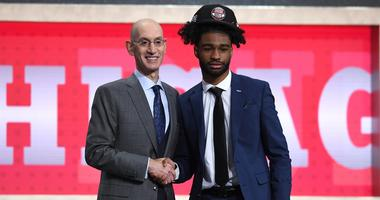 NBA commissioner Adam Silver congratulates Coby White after the Bulls selected White at No. 7 in the NBA Draft.
