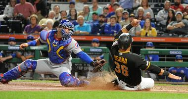 Pirates infielder/outfielder Jose Osuna (36) slides past the tag of Cubs catcher Wilson Contreras (40) for a run.