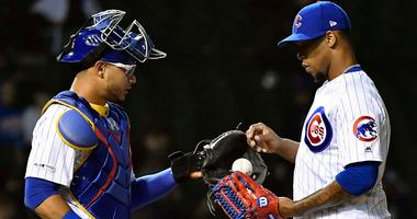 Cubs catcher Willson Contreras (40) hands the game ball to reliever Pedro Strop (46).
