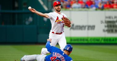 Cardinals shortstop Paul DeJong turns a double play as Cubs catcher Willson Contreras slides into second base.