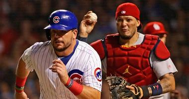 Cubs outfielder Kyle Schwarber is caught in a rundown as Cardinals catcher Yadier Molina pursues him.