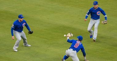 Cubs shortstop Javier Baez (9) tries to catch a single hit by Braves catcher Brian McCann.