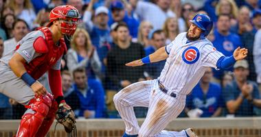 Cubs infielder David Bote (13) slides in safely to score a run against the Cardinals.