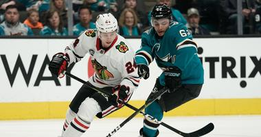 Blackhawks center Dominik Kahun (24) and Sharks right wing Kevin Labanc (62) fight for control of the puck.