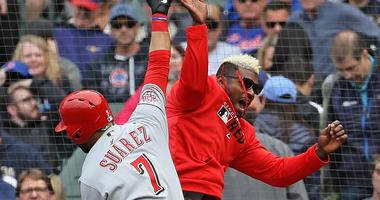 Eugenio Suarez (7) celebrates with Reds teammate Yasiel Puig after hitting a go-ahead homer against the Cubs.