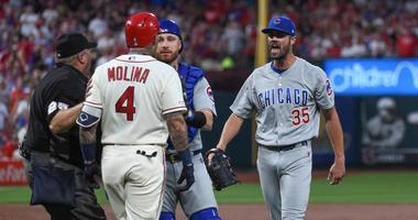 Umpire Fieldin Culbreth (25) and Cubs catcher Jonathan Lucroy (25) attempt to stop Cardinals catcher Yadier Molina (4) from confronting left-hander Cole Hamels (35) after being hit by a pitch.