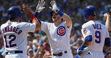 Cubs infielder/outfielder Ian Happ is greeted by teammates after hitting a grand slam against the Athletics.