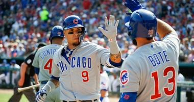 Cubs shortstop Javier Baez (9) is greeted at the dugout by third baseman David Bote (13) after hitting a solo home run.