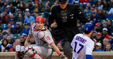 Cubs third baseman Kris Bryant (17) slides safely into home plate to score ahead of a tag by Phillies catcher J.T. Realmuto (10).