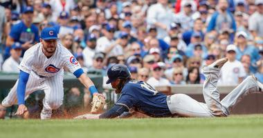 Brewers outfielder Ben Gamel (16) steals third base ahead of a tag by Cubs third baseman Kris Bryant (17).