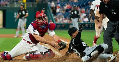White Sox center fielder Leury Garcia (28) slides home past the tag attempt of Phillies catcher J.T. Realmuto.