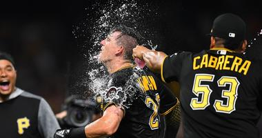 Pirates shortstop Kevin Newman (27) celebrates with teammates after his walk-off single to beat the Cubs.