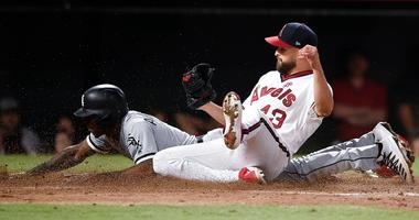 White Sox shortstop Tim Anderson (back) dives to score past Angels starting pitcher Patrick Sandoval (43) on a wild pitch.