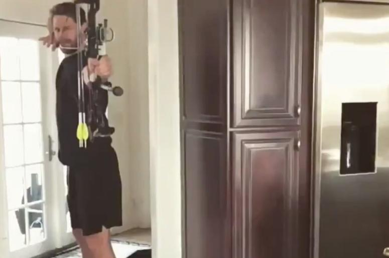 Chase Rice shooting a bow and arrow