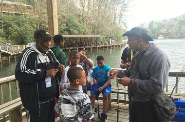 Officer Bruce Griggs (l)  observes as the boys receive fishing lessons at YMCA Camp High HarboUr in Cartersville GA