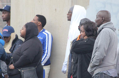 Rapper Young Thug (white hoodie) is among a group of onlookers at the scene of a deadly double shooting