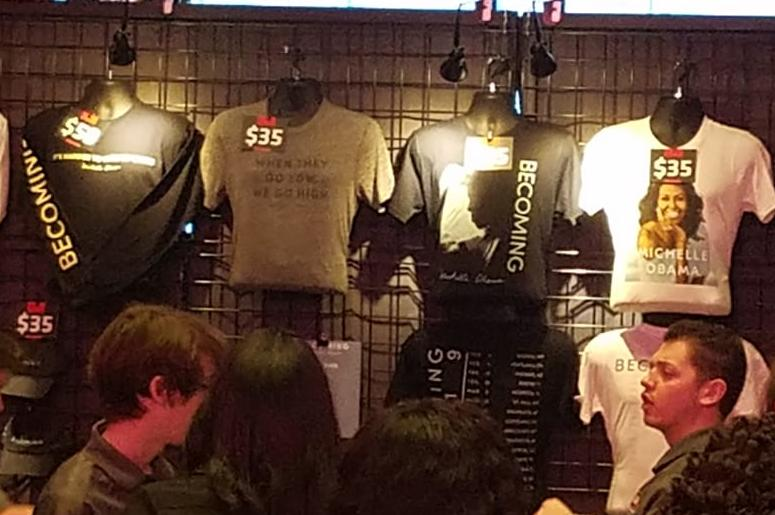 """Similar to a concert, event-goers stood in line to purchase merchandise showcasing the """"Becoming"""" tour event."""