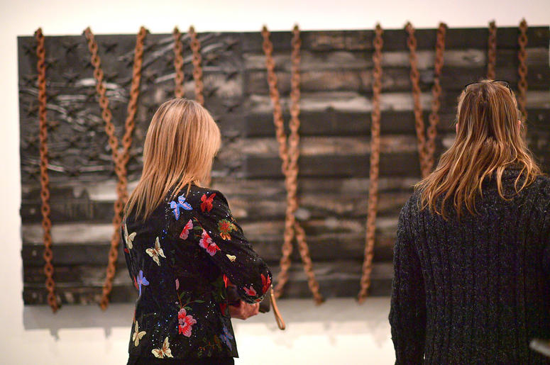 """Attendees admire artwork created by D.L. Warfield, displayed during his """"My Favorite Things"""" art exhibit on November 30, 2018, in Atlanta."""