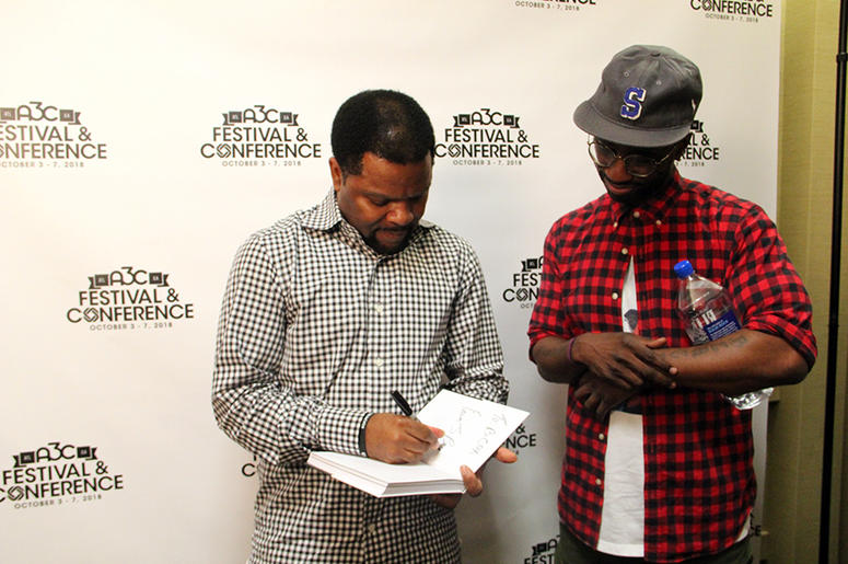 Rap-A-Lot Records founder J. Prince signs a copy of his book for producer Bryan-Michael Cox at A3C in Atlanta on October 4, 2018