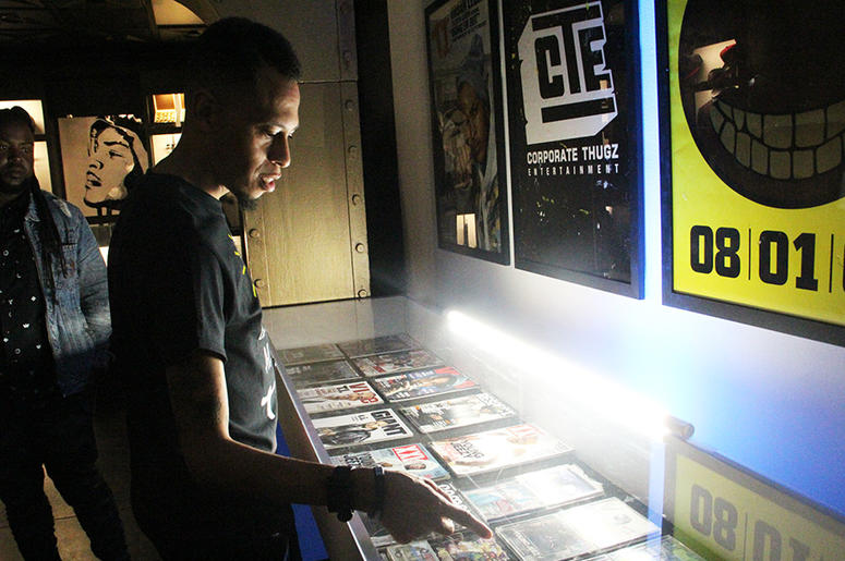 """Hip-hop collector Larry """"Nuface"""" Compton points to an exhibit holding magazines from his personal collection in T.I.'s Trap Music Museum in Atlanta"""