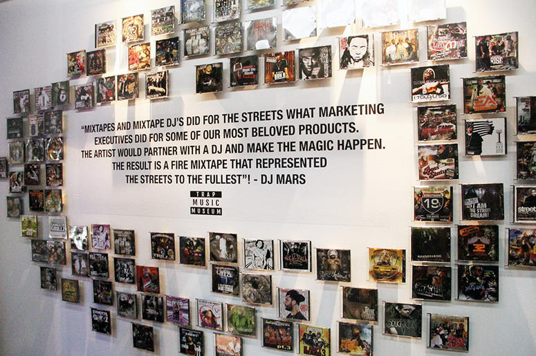 A wall of rap mixtapes surrounds a quote from DJ Mars inside T.I.'s Trap Music Museum in Atlanta