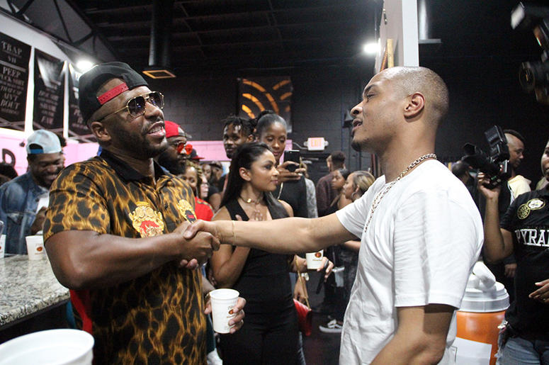 Atlanta rapper Rocko shakes hands with T.I. inside the Trap Music Museum