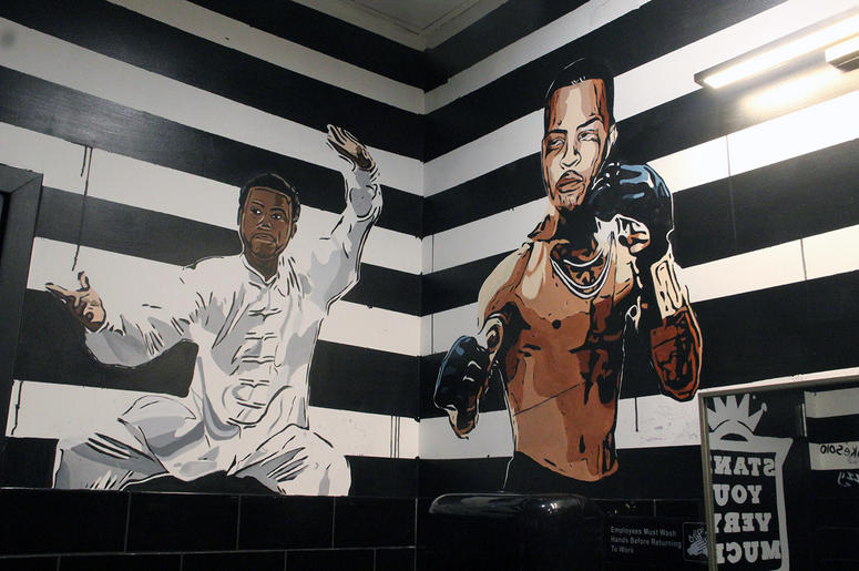A mural of Gucci Mane and T.I. in Slim & Husky's bathroom