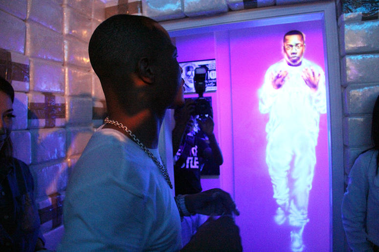 T.I. looks at a glowing mural of Memphis rapper Yo Gotti inside his Trap Music Museum