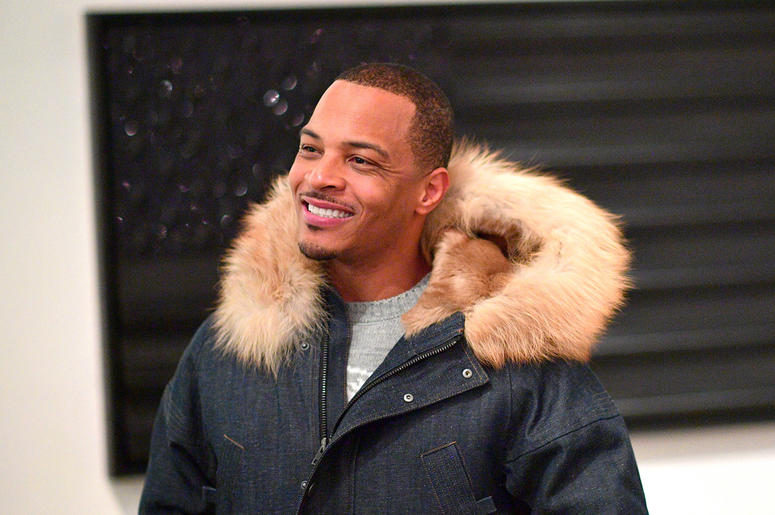 """T.I. admires artwork created by D.L. Warfield, displayed during his """"My Favorite Things"""" art exhibit on November 30, 2018, in Atlanta."""