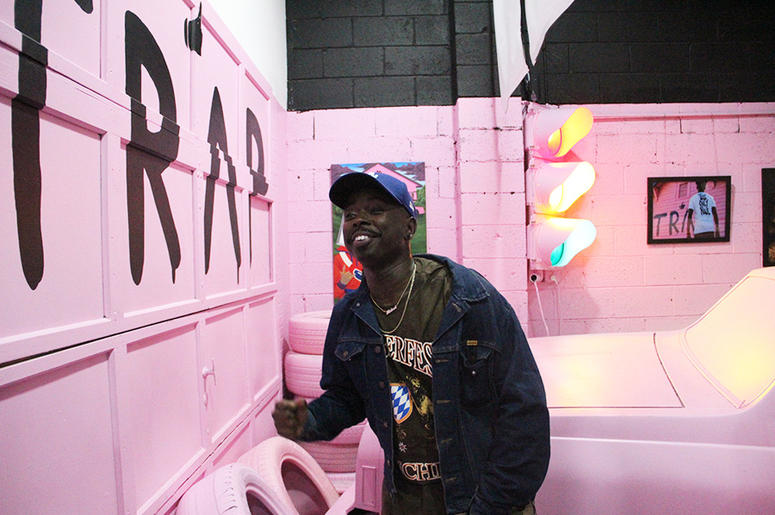 A man smiles while sitting on 2 Chainz's pink Chevy inside T.I.'s Trap Music Museum