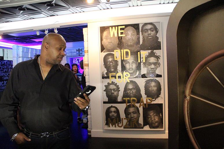 Man stands near large framed artwork of 12 prominent trap artists at T.I.'s Trap Music Museum