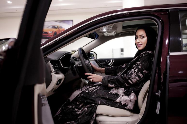 Maram Al-Hazer poses for a photograph inside a Lincoln Continental at Al-Jazirah Ford