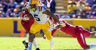Nov 11, 2017; Baton Rouge, LA, USA; LSU Tigers running back Derrius Guice (5) avoids the tackle of Arkansas Razorbacks defensive back Santos Ramirez (9) and defensive lineman Briston Guidry (8) in the first quarter at Tiger Stadium.