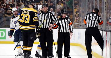 Referee Steve Kozari reviews the play during the third period in Game 5 of the 2019 NHL Stanley Cup Final between the Boston Bruins and the St. Louis Blues.